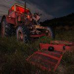 Fotografía nocturna de un tractor rojo abandonado