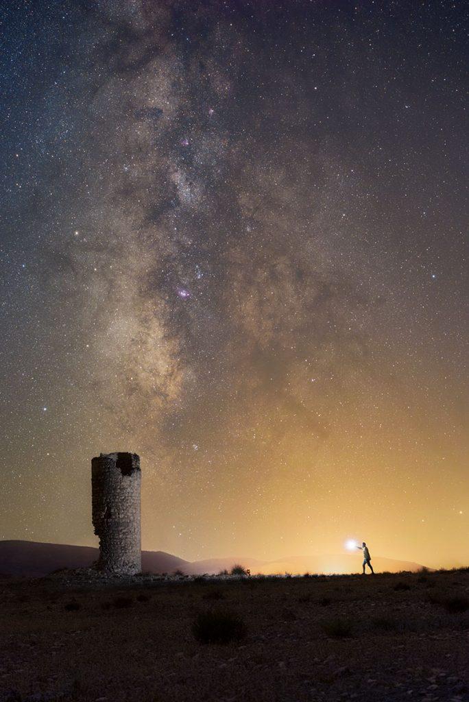Fotografía nocturna de la torre del Salar de Orce con la vía láctea al fondo